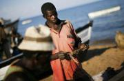 A fisherman stitches his fishing net on May 14, 2008. Fishing is a key source of employment in Africa's impoverished nations