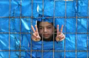A Syrian refugee child flashe the V sign from behind a fence at the refugee camp in Yayladagi on March 26, 2012. ©BELGA/AFP/A.Altan