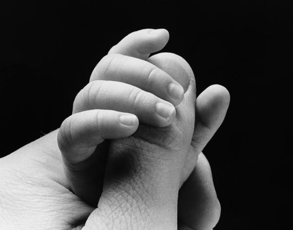 La mano de un bebé coge el dedo de un adulto