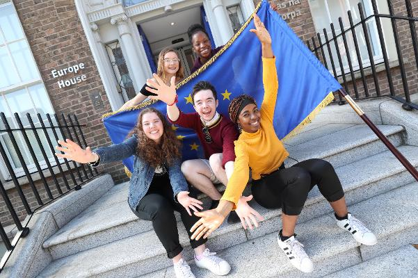 Young people with European flag on steps of Europe House Dublin