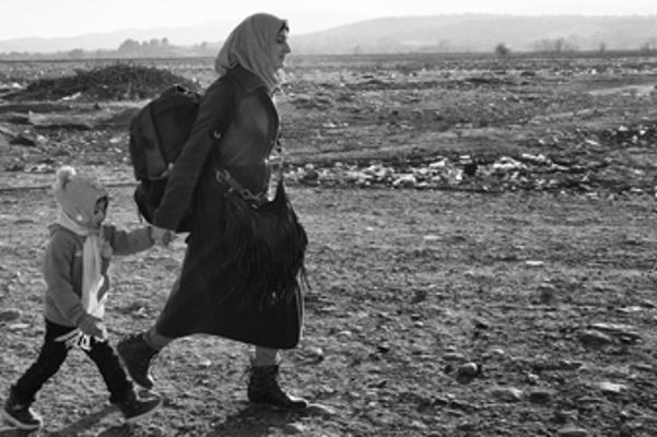 picture of woman with backpack walking with child (black and white)