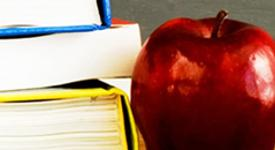 Apple beside schoolbook