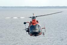 Coastguard helicopter flying over water.