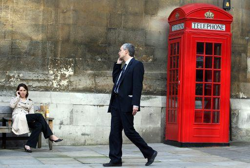 A man and a woman speak on cell phones near a telephone booth in London, UK.  ©BELGA/MAXPPP/Adam Berry