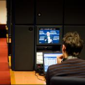 A journalist is watching the one minute speech life streamed from the Plenary Chamber in the EP press room