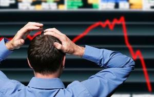 Stocktrader clutching his head in front of a screen showing a stock market crash ©BELGA_imagebroker_Simon Belcher