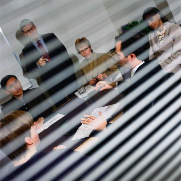Employees in a meeting, seen through blinds ©Getty Image