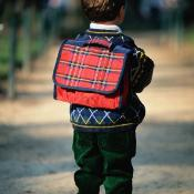 Small boy with a tartan rucksack on his back