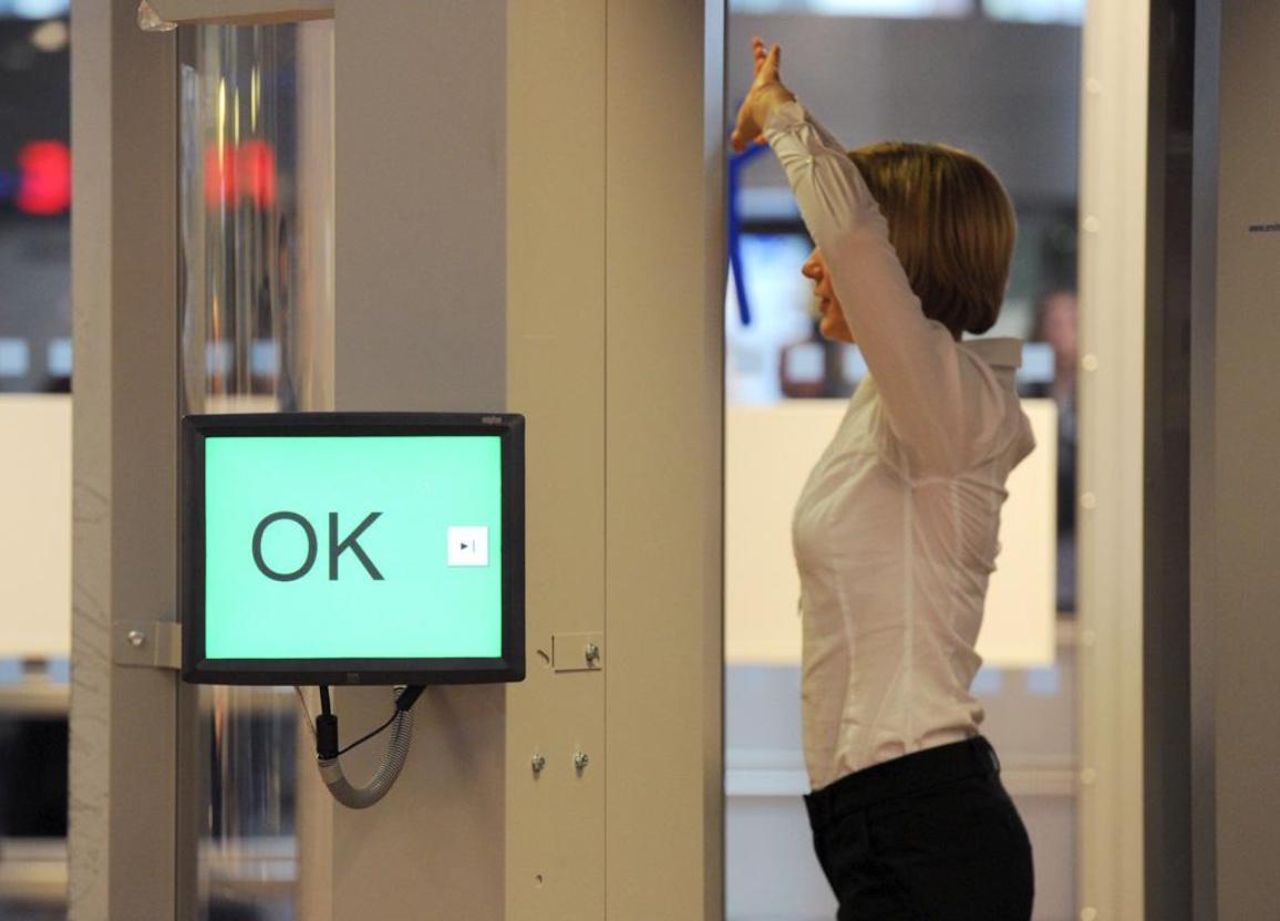 Nainen henkilöskannerissa, nostaa käsiään ylös. ©BELGA/DPA/A.WARMUTH
