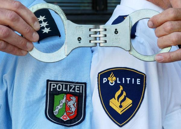 Officers pose in uniform with handcuffs during police training of the German and Dutch police