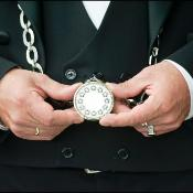 A view of an usher holding a pocket watch with 12 stars
