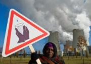Hauwa Umar-Mustapha from Nigeria, witnesses to climate change, protests the shortage of drinking water in front of the cooling towers of the brown coal power plant of power company Vattenfall AG in Jaenschwalde, Germany ©EPA/PATRICK PLEUL