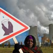Hauwa Umar-Mustapha from Nigeria protests shortage of drinking water in front of the cooling towers of the brown coal power plant of power company in Germany ©EPA/PATRICK PLEUL