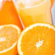glass of orange juice surrounded by orange slices