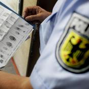 A police officer observes finger prints at a border police station in Aachen, Germany, 27 May 2011. ©BELGA_DPA