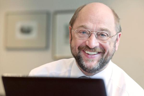 A smiling Martin Schulz sitting behind a computer