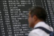 A man stands in front of the flight information board which informs about cancelled flights at Frankfurt airport