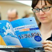 Woman looks at leaflet regarding Citizens' Initiative