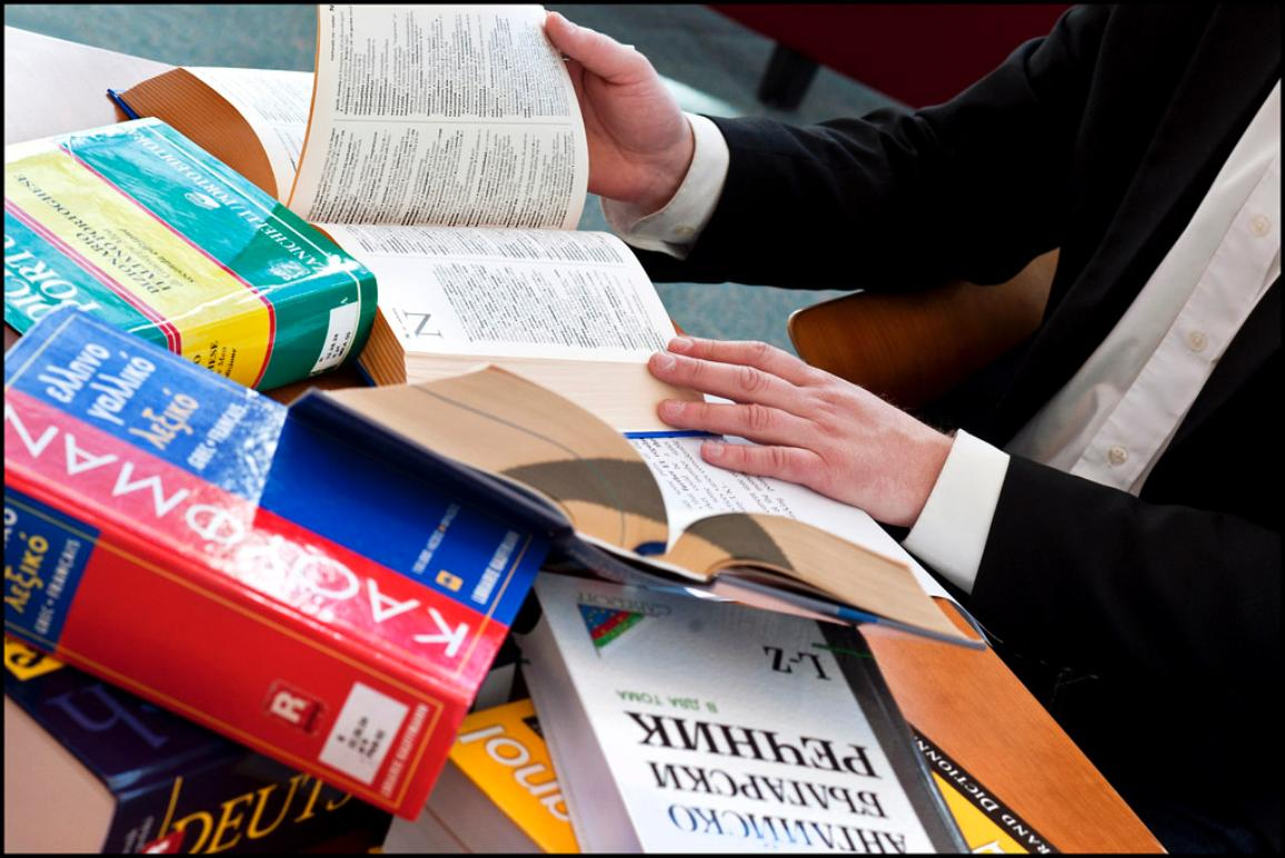 Man consulting pile of books