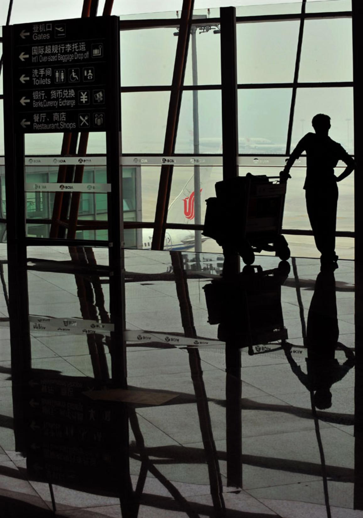 A traveler looks out of a window at the tarmac of an airport © BELGA_AFP_TEH ENG KOON