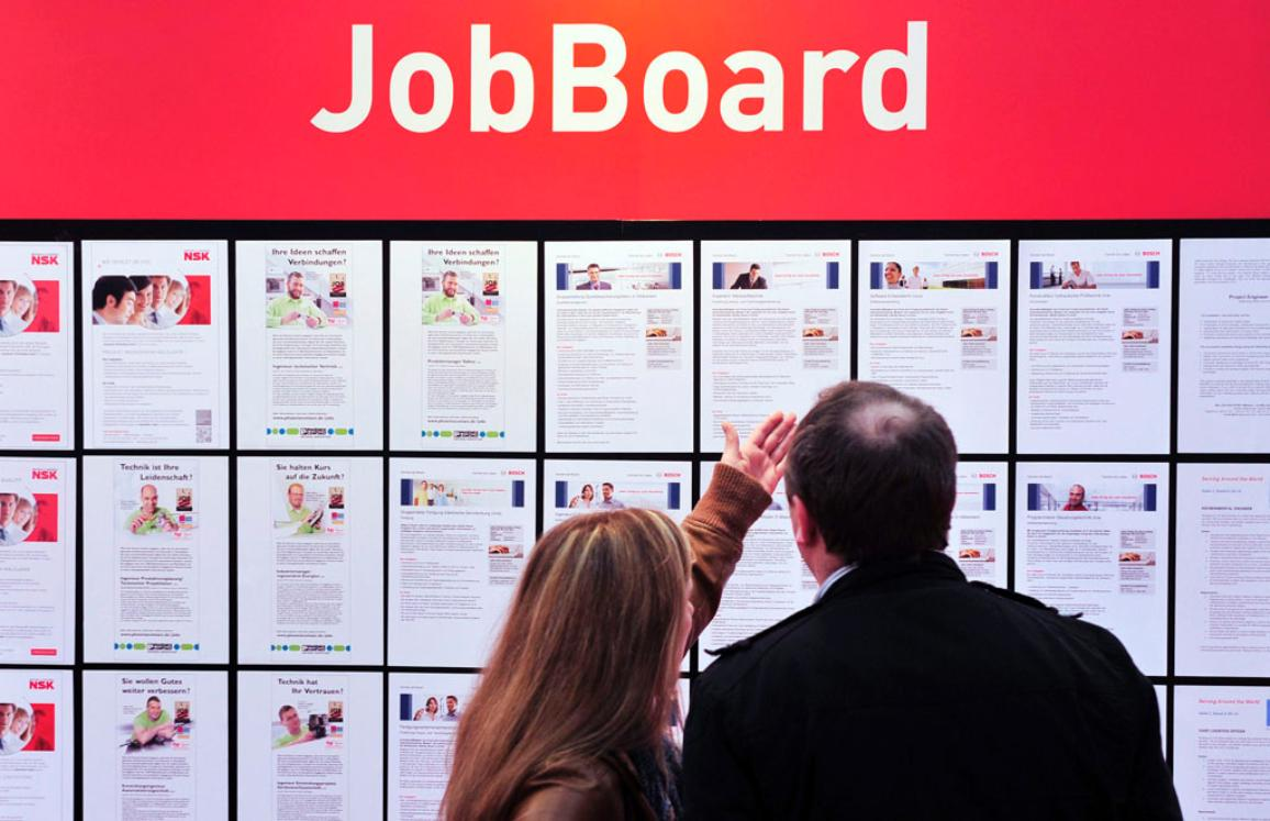 Visitors consult a board with job offers at the Hanover Fair in Hanover, Germany