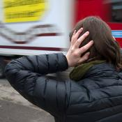 A woman holds her ears as a lorry drives by in busy traffic