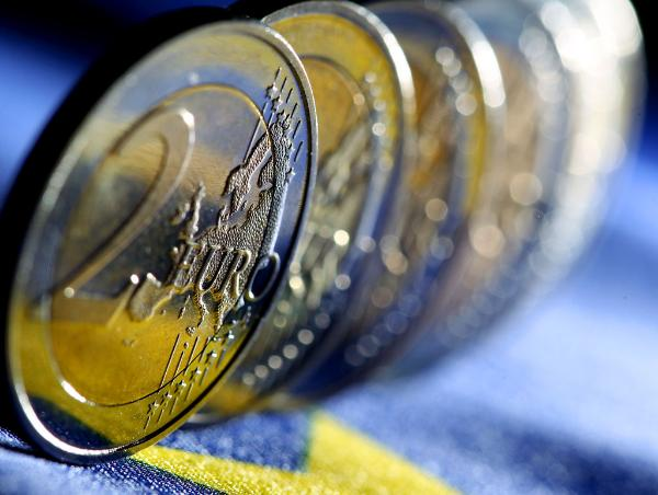 Euro coins sitting on a European flag
