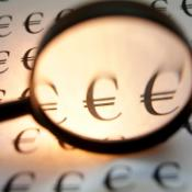 Euro signs under a magnifying glass