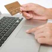 Une femme tient une carte de crédit et utilise un ordinateur portable
