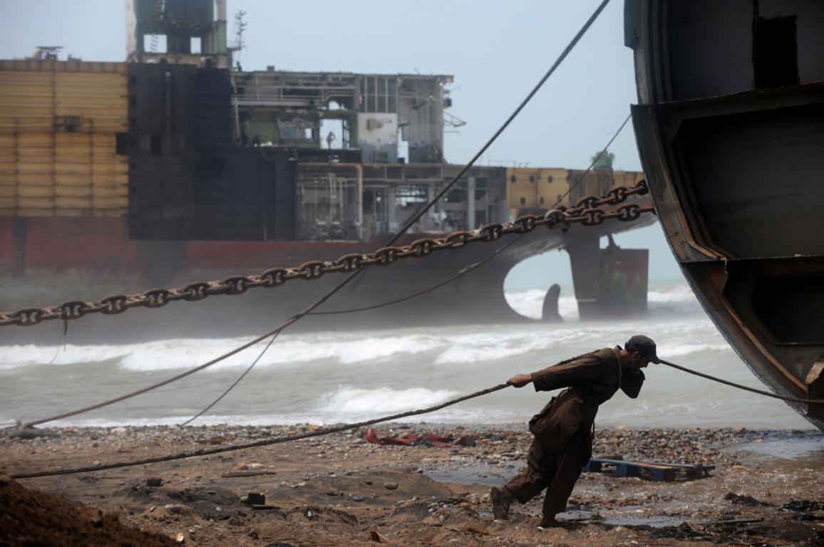 Ein Mann zieht an einem Seil, das an einem Schiffswrack befestigt ist