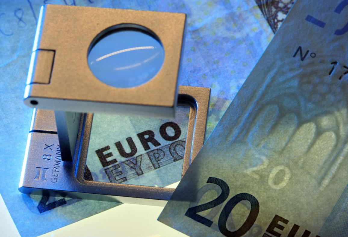 Imagen de dos billetes de veinte euros bajo una lupa. © BELGA_J.Buettner