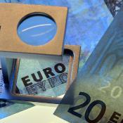Billets de banque en euros sous une loupe