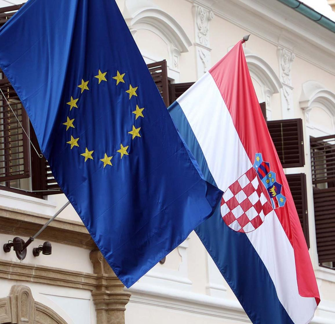The flags of the European Union and Croatia fly at the Croatian Government building in Zagreb