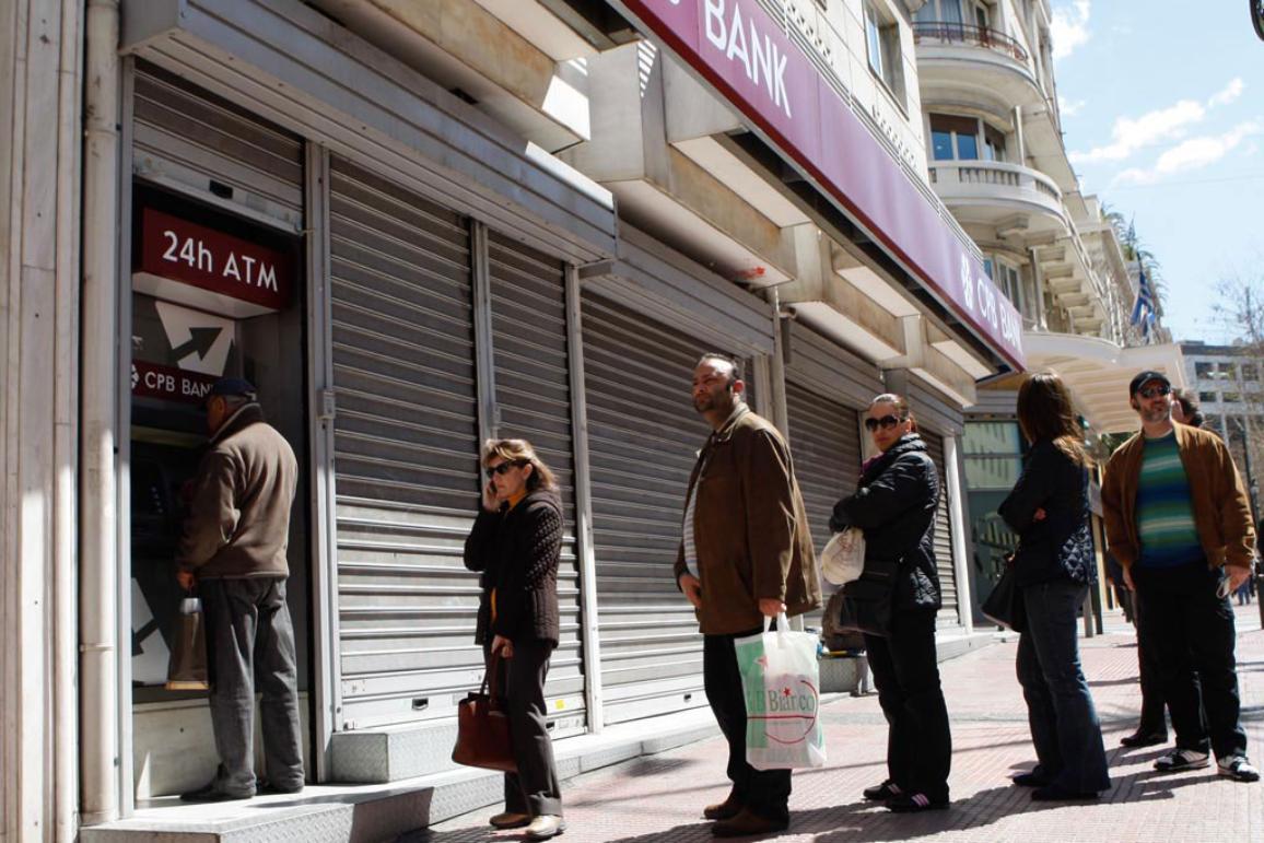 Pessoa numa fila em frente a um multibanco de um banco fechado ©Belga/Zumapress/A.Vafeiadakis