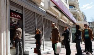 People queuing in front of an ATM at a closed bank ©Belga/Zumapress/A.Vafeiadakis