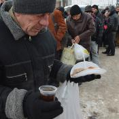 Homeless people queue to get a free hot meal