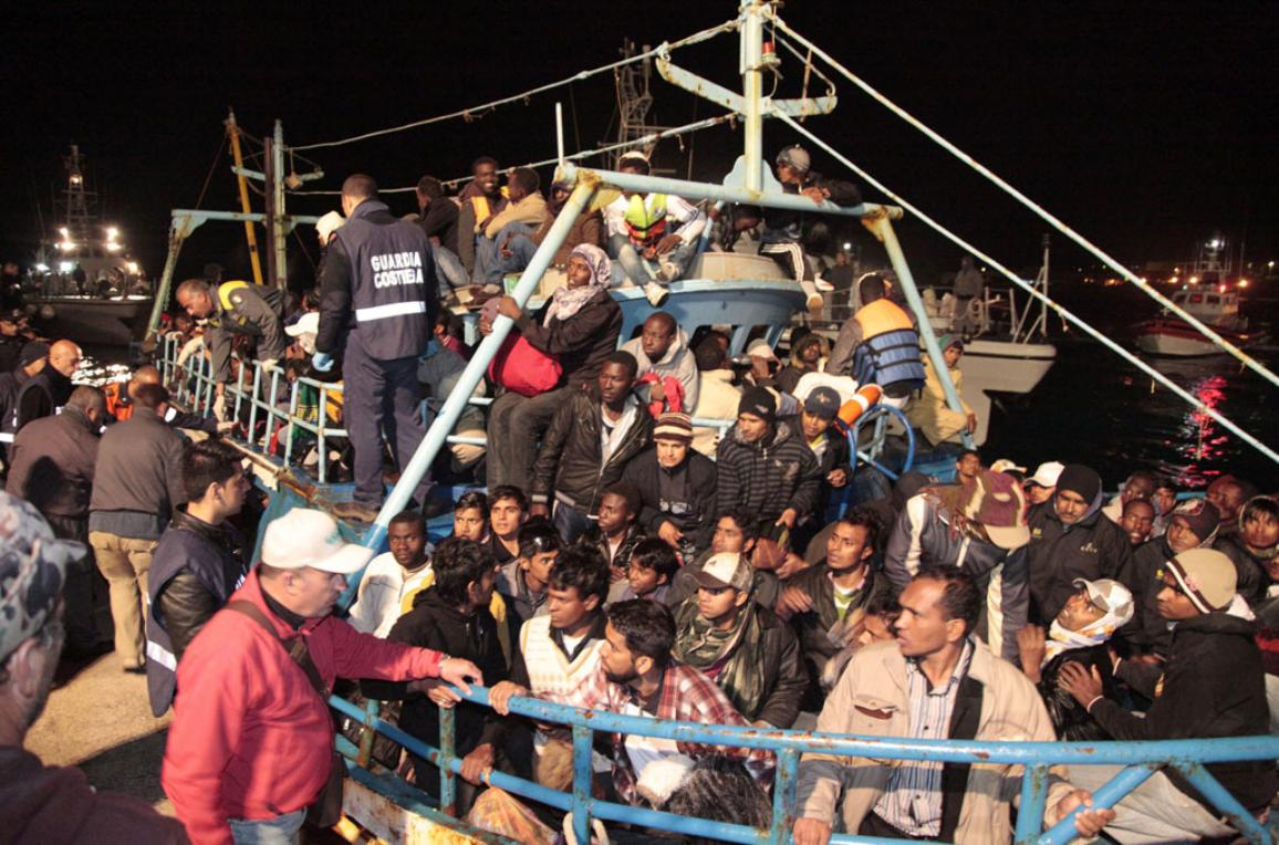 Italian coastguards look on as a boat full of refugees arrives