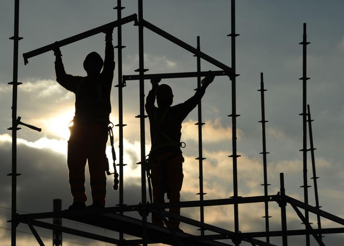 Two men standing on a scaffolding during construction works ©BELGA/AFP/C.STACHE