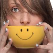 Woman holding a bowl with a smiley on it