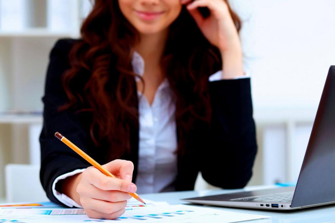 Töissä oleva nainen istumassa lehtiön kanssa.