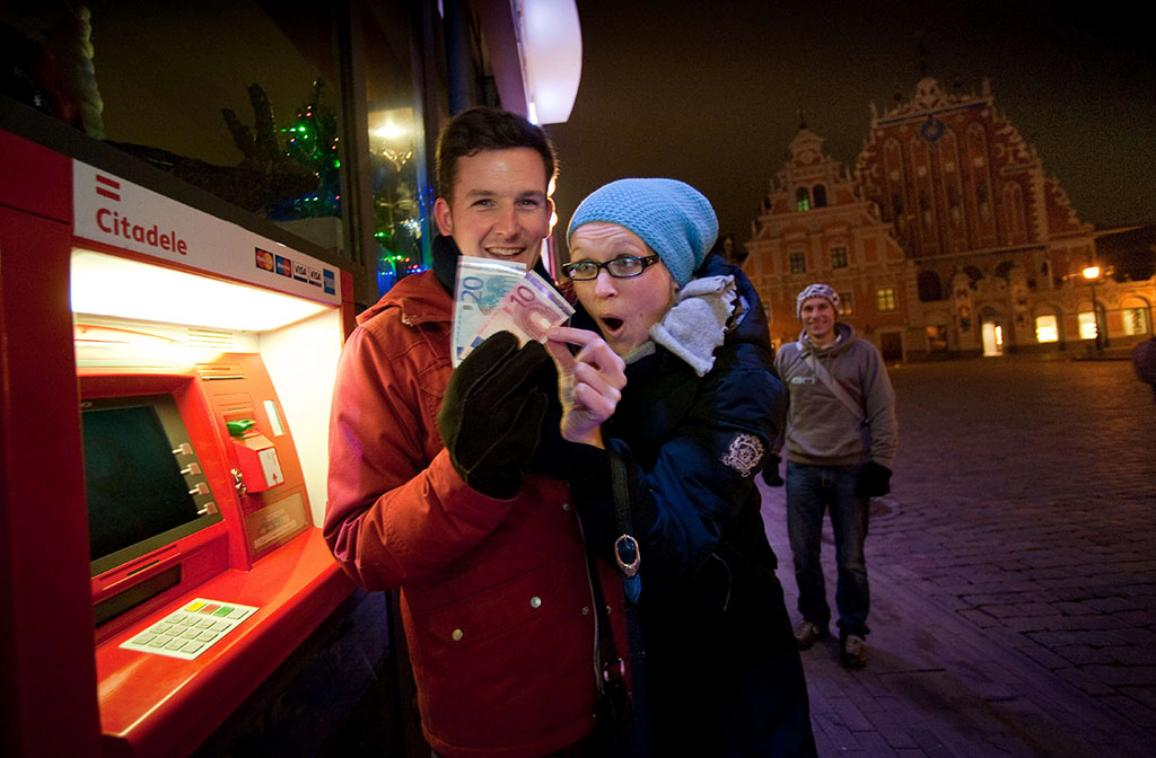 A young people displays euro banknotes after withdrawal on January 1, 2014 in Riga