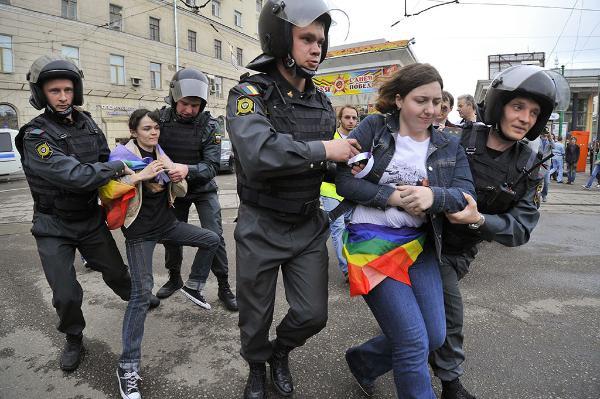 Photo de deux femmes ayant le drapeau arc-en-ciel LGBT noué autour de la taille, arrêtées par des policiers russes