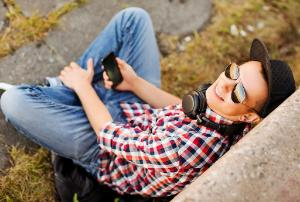 Teenager with headphones and smartphone outside