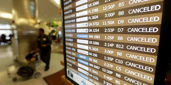 The flight board at Louis Armstrong International Airport show all flights cancelled