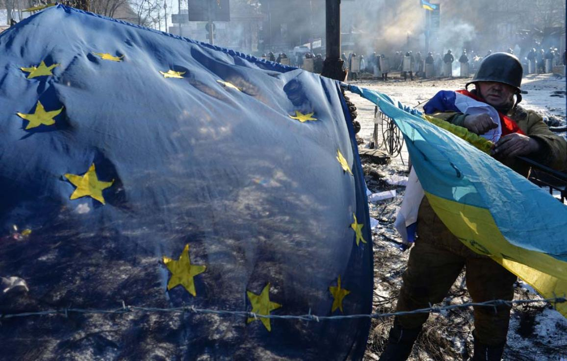 An anti-government opposition activist places European Union and Ukrainian flags side by side at a barricade in the Ukrainian capital of Kiev on February 2, 2014. ©BELGA_AFP_SERGEI SUPINSKY