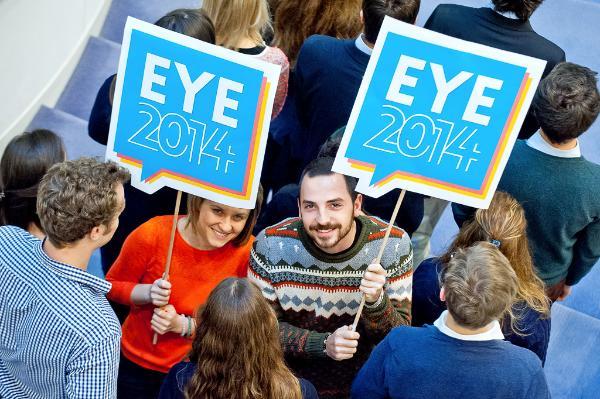 Photo de deux jeunes dans une foule portant des panneaux avec le logo EYE2014