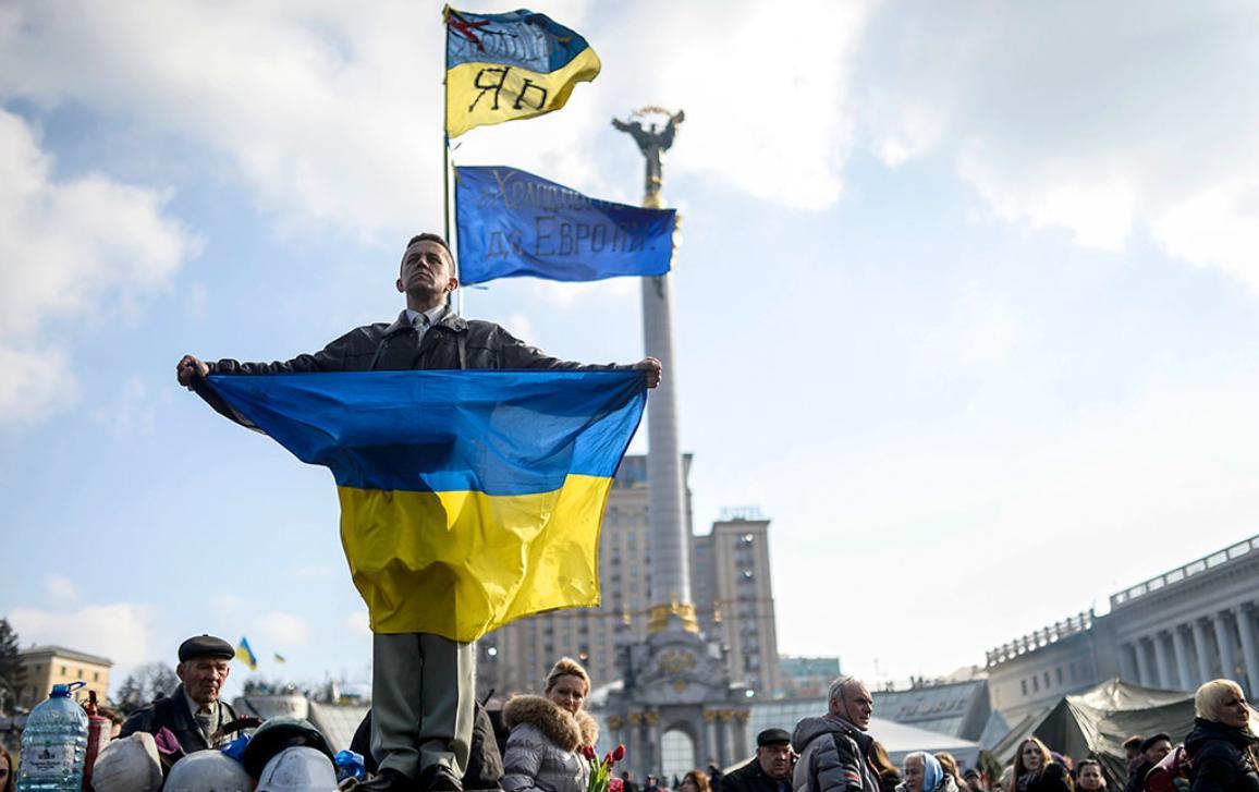 Ukrainos vėliavą laikantis protestuotojas Nepriklausomybės aikštėje Kijeve © BELGAIMAGE/AFP/B.KILIC