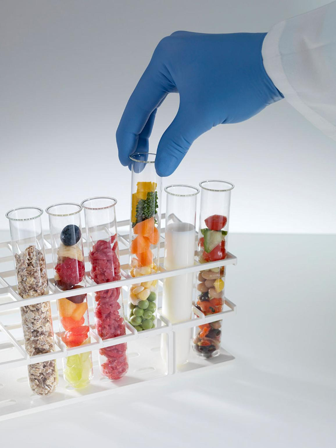 Scientist selecting a test tube containing vegetables