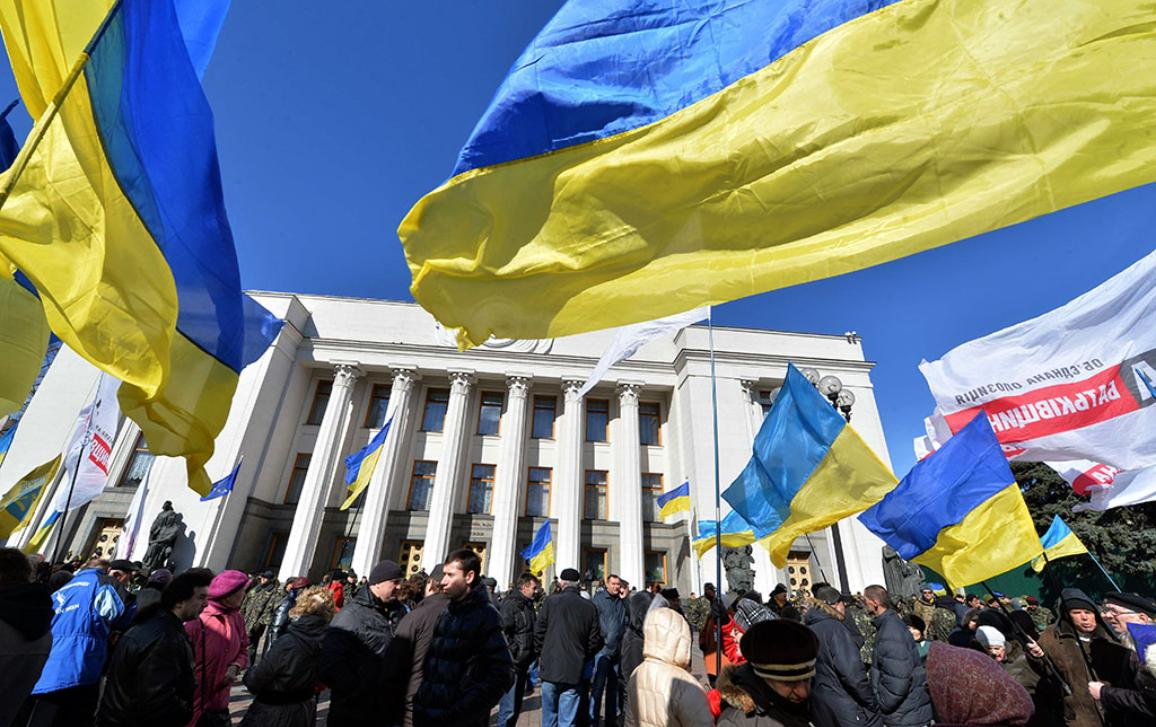 People hold Ukrainian flags as they gather in front of the parliament in Kiev