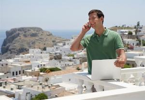 showing a guy on the phone with portable computer in the other hand on a Greek Island